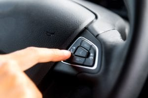 Person pressing cell phone button on steering wheel