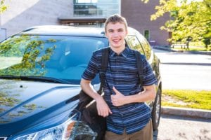 Teenage boy smiling and standing next to car