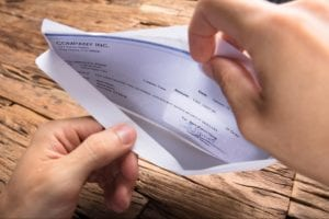 Person opening a check in an envelope from small claims court win