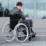 Man in wheelchair with face in hands