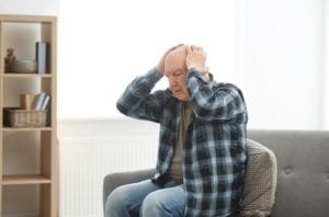 Stressed elderly man holding his head