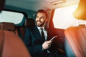 Businessman with phone on hand sitting on the backseat of the car