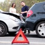 Two drivers examining car body damages after rear end accident