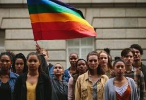 LGBTQ community with pride flag on city street