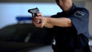 Police officer points gun