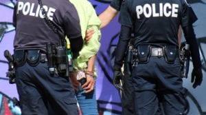 Multiple police officers arrest someone