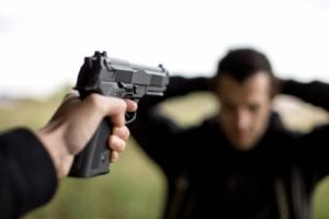 Man pointing a gun to another man with hands on his head