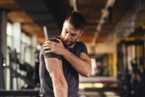 Man feeling pain in the shoulder at the gym