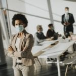 Woman with a mask on stands by conference table