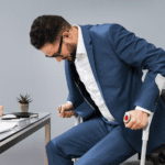 Man with leg injury getting up from a chair