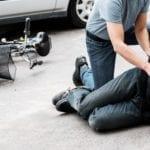 Pedestrian helping a victim of an accident next to a broken bike