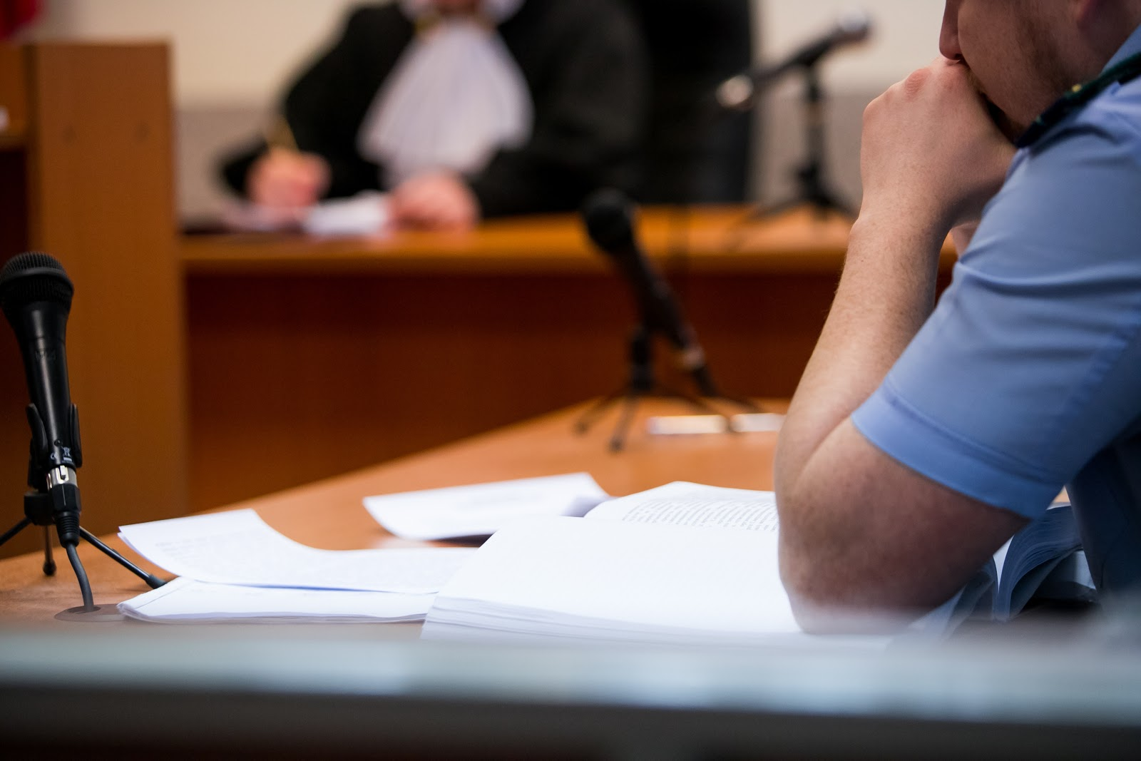 Policeman sitting inside a courtroom