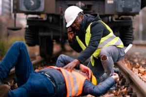 Injured worker lying on the ground while his coworker calls for help