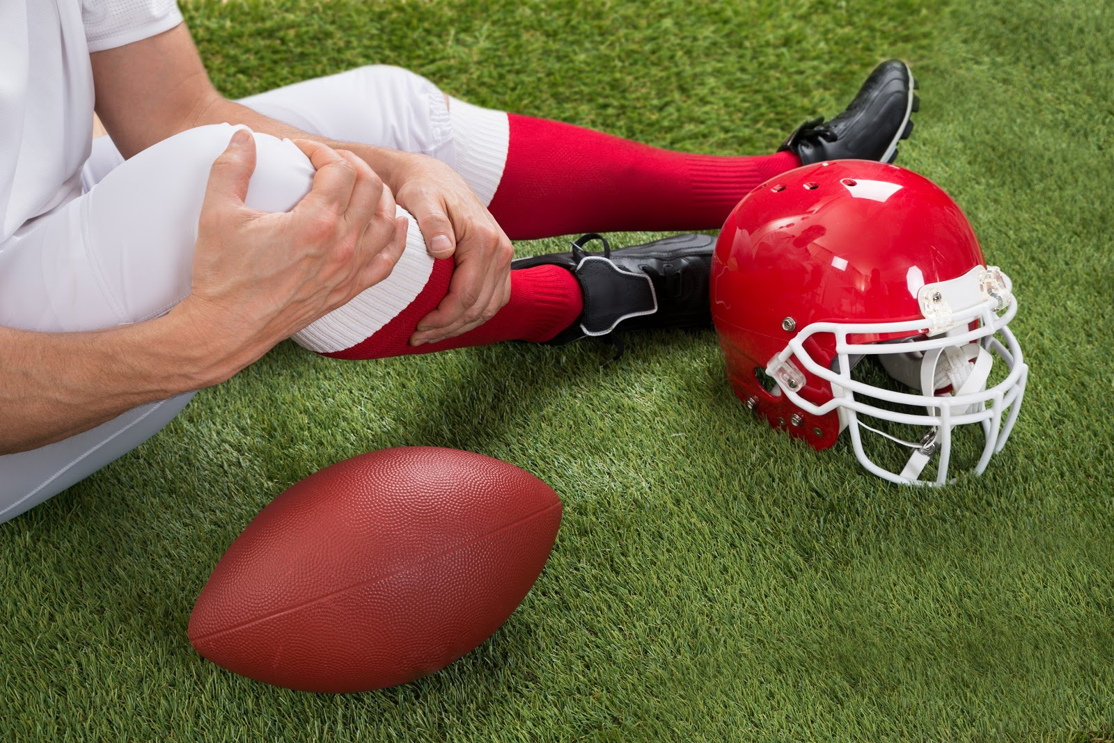 Football player holding his injured knee