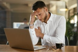 Man looking at his laptop in worry while holding his head in his hand