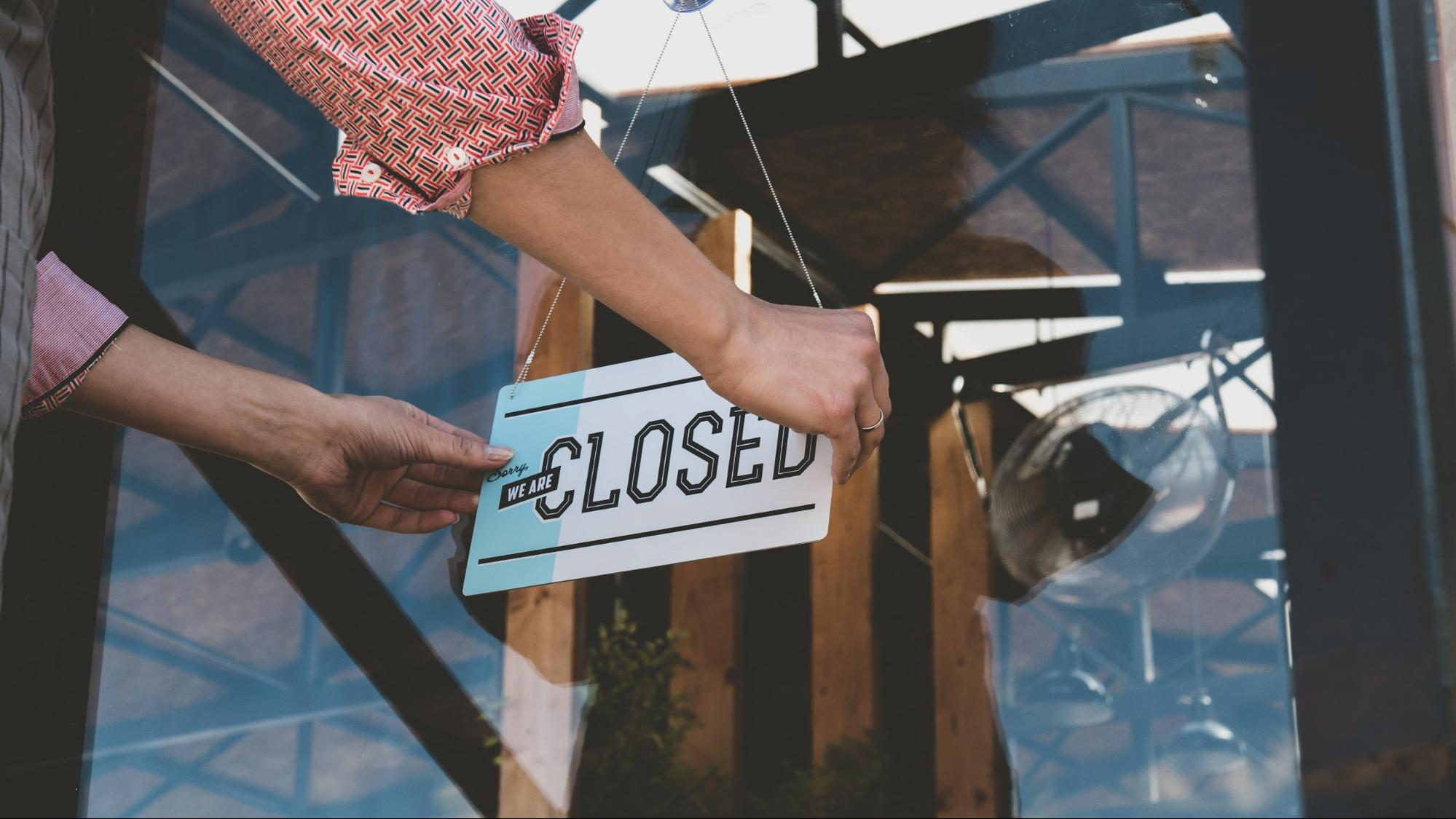 Business owner hanging a closed sign on the door
