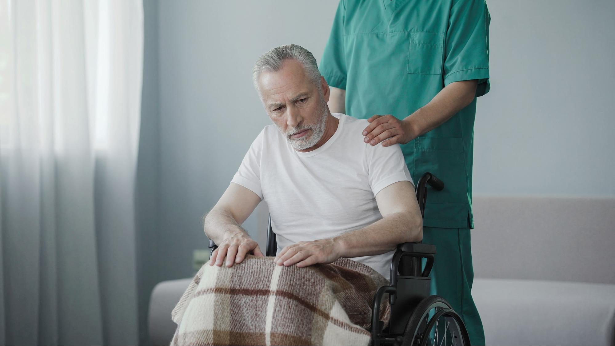 Injured elderly man in a wheelchair being assisted by his nurse