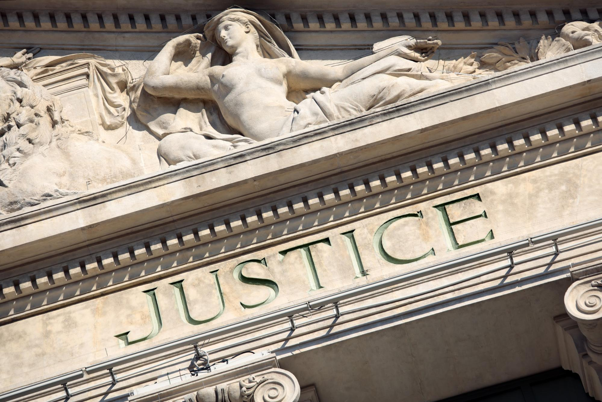 The word justice engraved in front of a courthouse