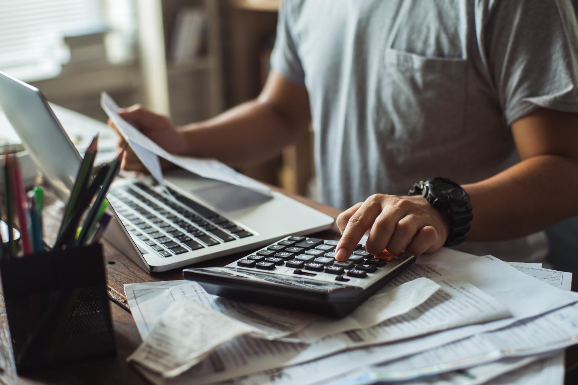Man computing his bills using a calculator at his desk