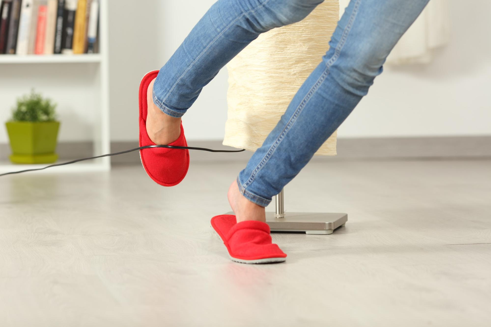 Woman tripping over a cord of a floor lamp
