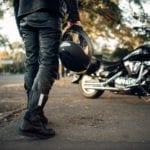 Motorcycle rider holding a helmet walking towards his motorcycle