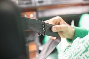 Hand holding a broken seat belt