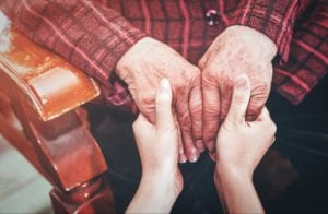 Young girl's hands holding the hands of an elderly