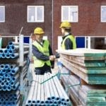 Two contractors shaking hands at a construction site