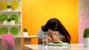 Woman feeling nauseous while eating