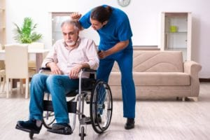 Old man in a wheelchair with an angry male caregiver
