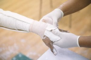Doctor's hands splinting a patient's broken arm