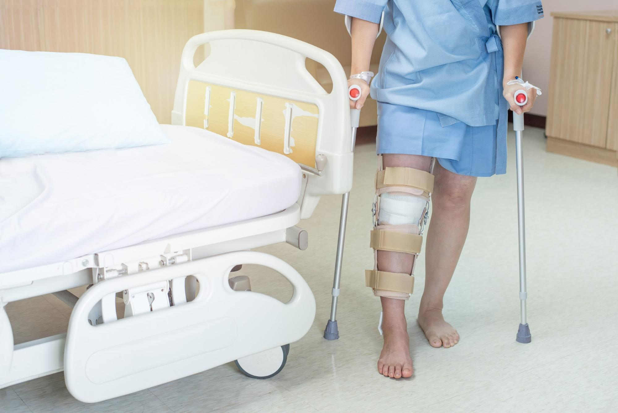 Patient with a knee brace and walking sticks in a hospital room