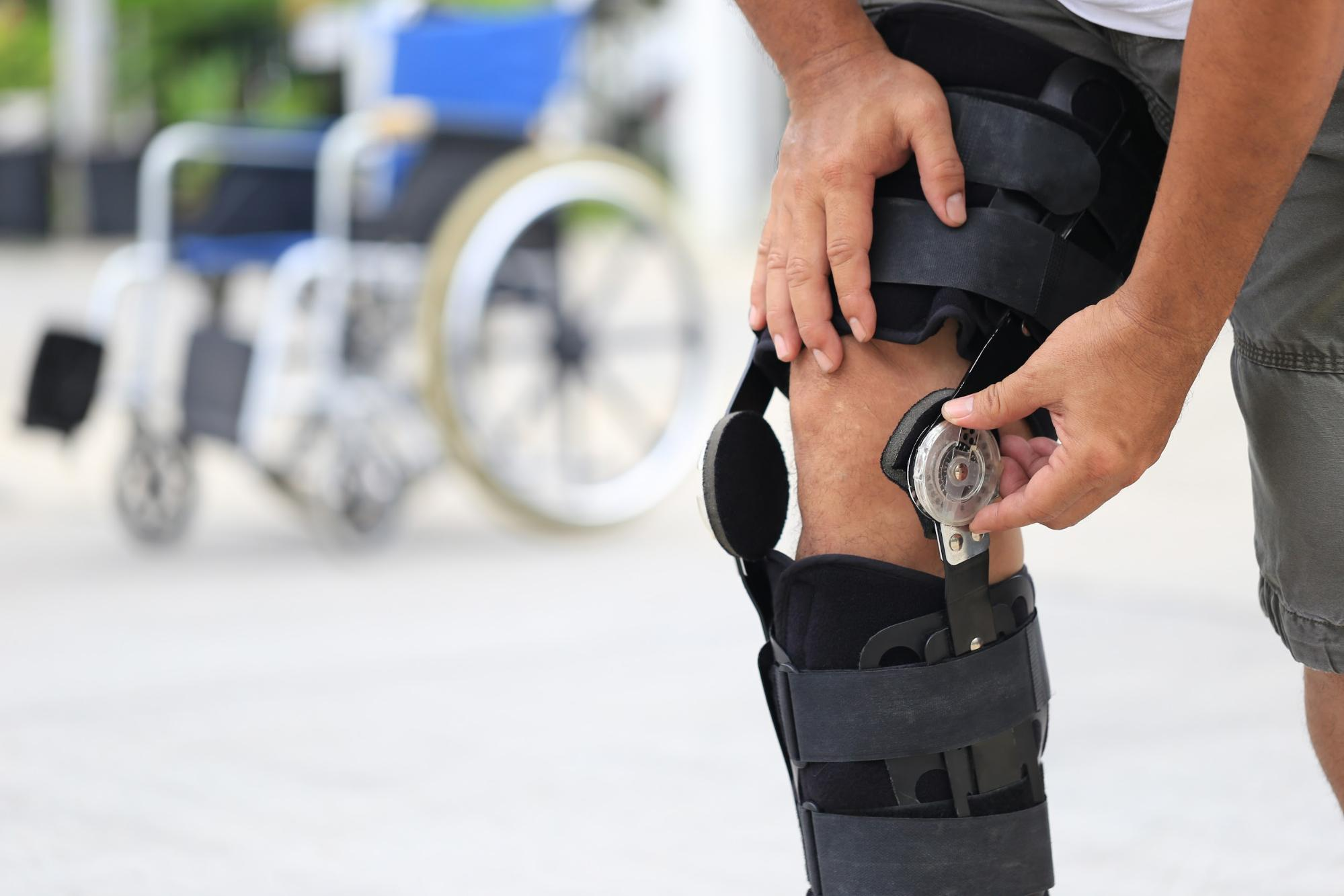 Man wearing a knee brace with a wheelchair in the background