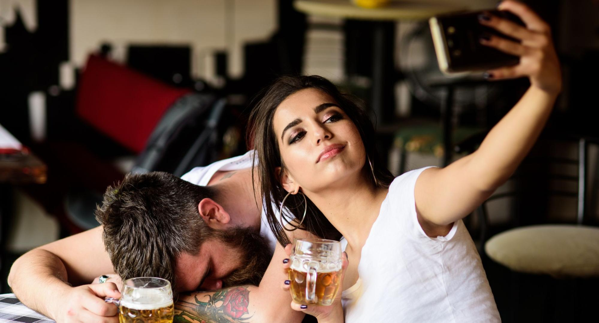 Woman taking a selfie with an intoxicated man behind her