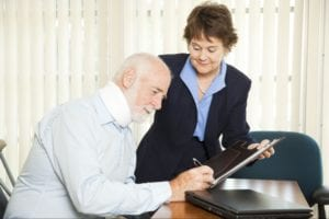 Woman assisting an injured elderly man as he signs a piece of paper