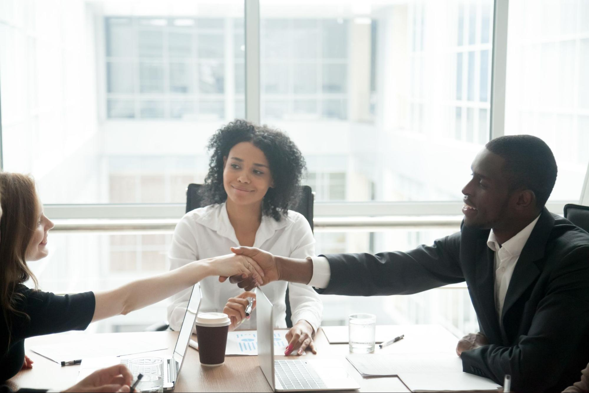 Woman smiling while her two colleagues shake hands