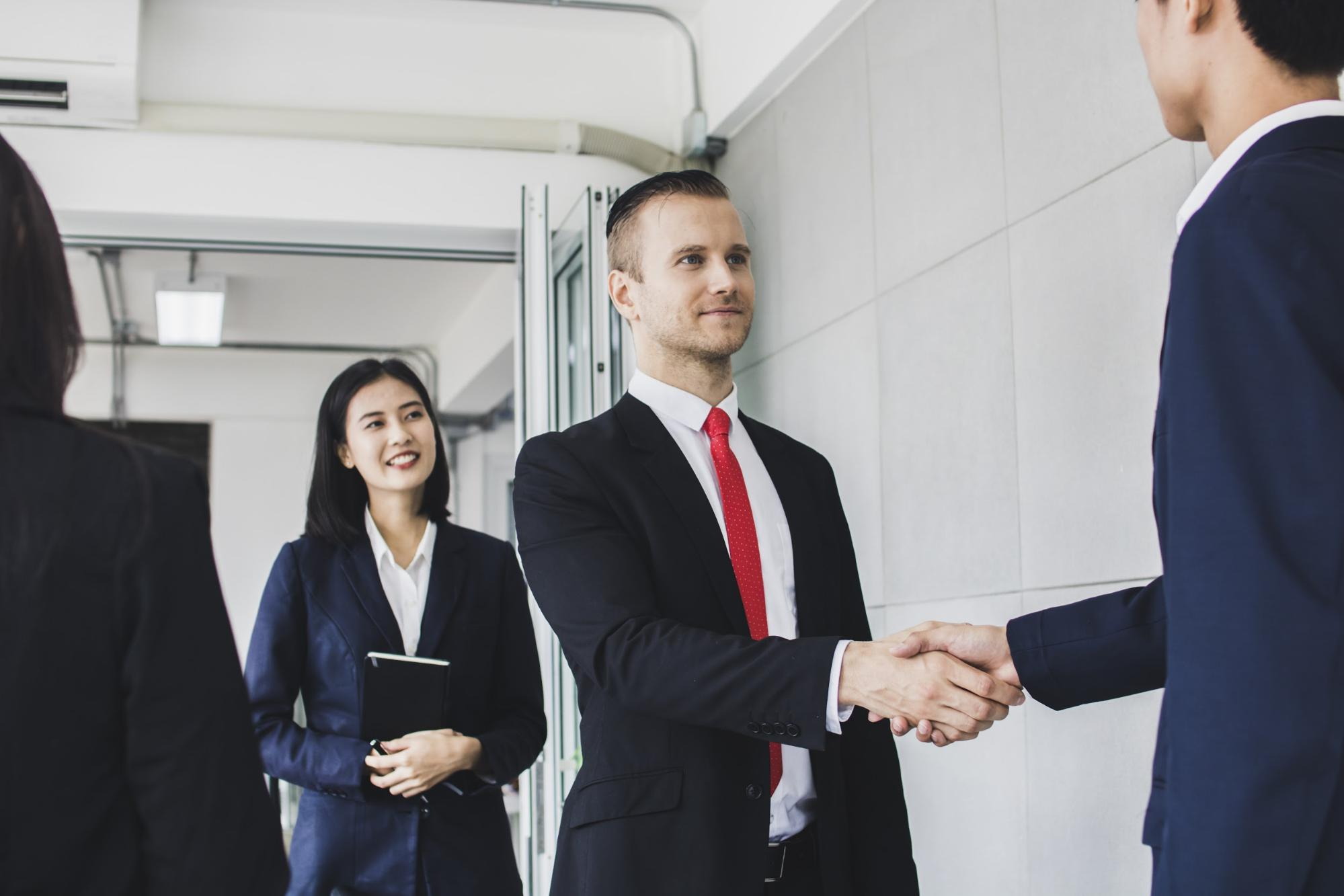 Businessmen shaking hands with one of their colleagues smiling near them