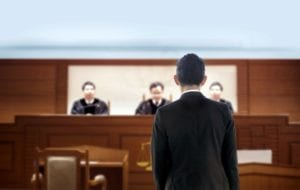 Man standing in front of the judges in a courtroom