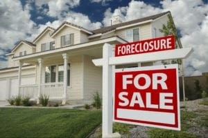 Foreclosed house with a for sale sign in front