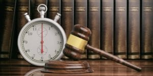 Stopwatch and gavel with books in the background
