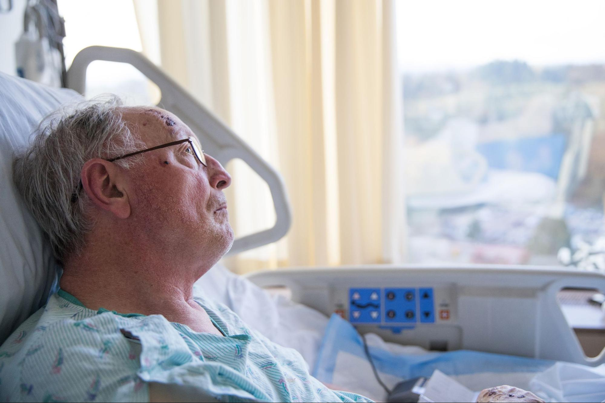 Elderly man looking out the window while lying in a hospital bed