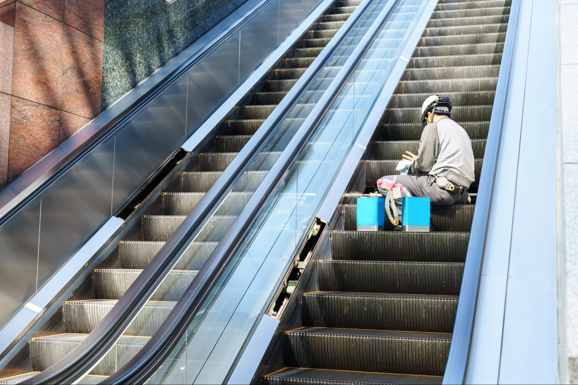 Maintenance person working on an escalator