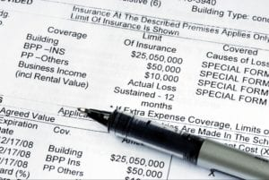 Black pen over a home property insurance policy