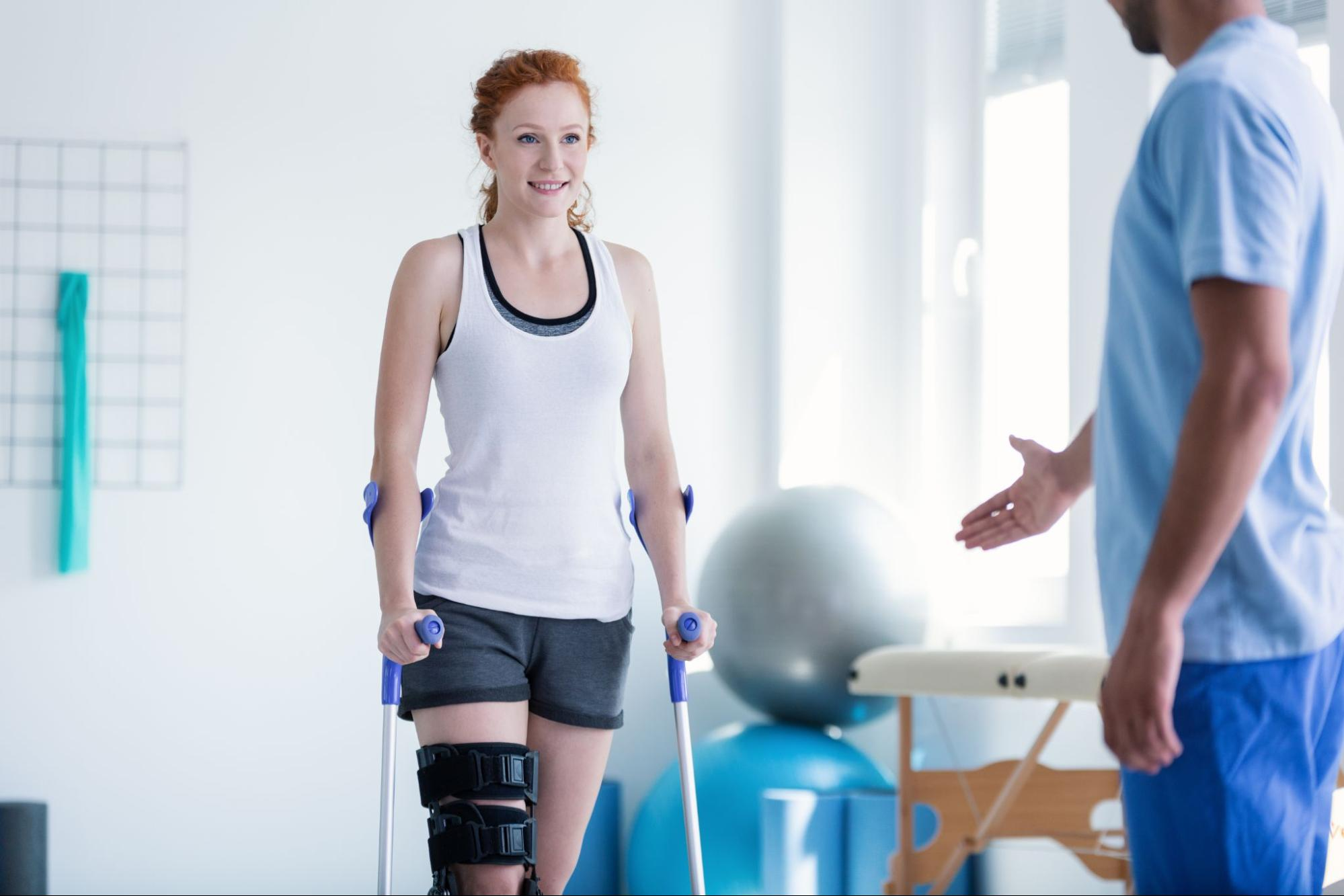Woman walking with crutches during a physical therapy session
