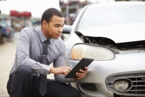 man looking at his car while holding a tablet