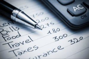 Pen and calculator over a list of expenses