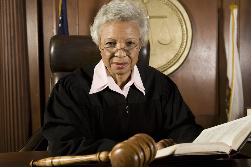 Elderly judge in a courtroom and looking at the camera