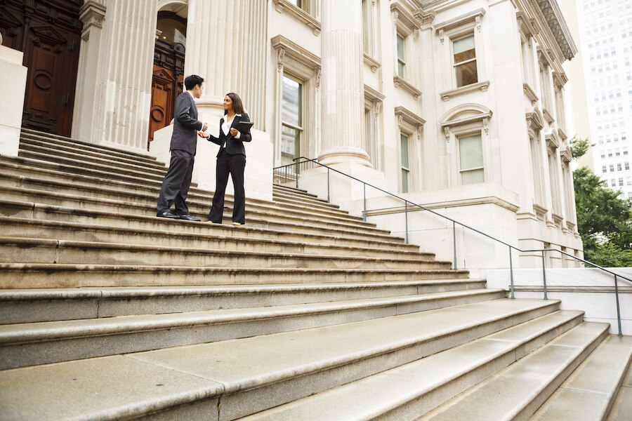 Two colleagues having a discussion on the front steps of a building