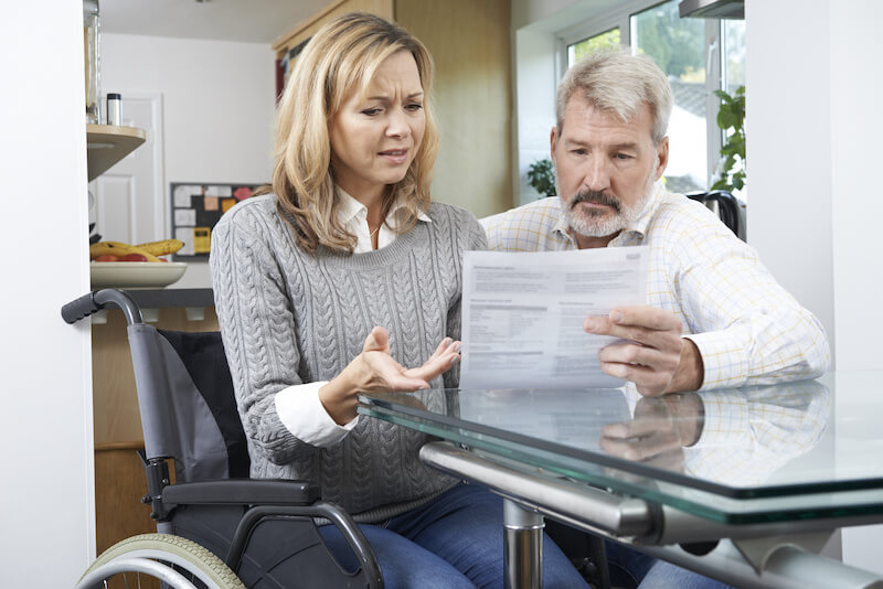 Woman in a wheelchair discussing a document with her husband