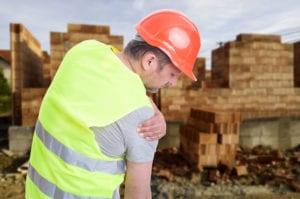 workers compensation shoulder injury settlements: Man holding his shoulder
